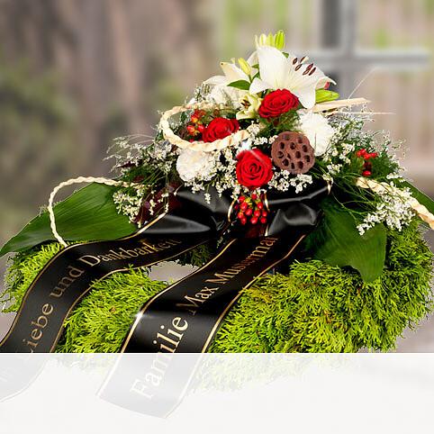 Trauerkranz mit roten Rosen und weißen Lilien